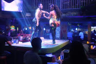 Dancers Leidy Manzano and Yasser Rodriguez perform on the bar at Mango's Tropical Cafe, Wednesday, Sept. 15, 2021, in Miami Beach, Fla. The Cafe has been in South Beach for 30 years and has been affected by pandemic restrictions and unruly street crowds that the city has been unable to control. (AP Photo/Marta Lavandier)
