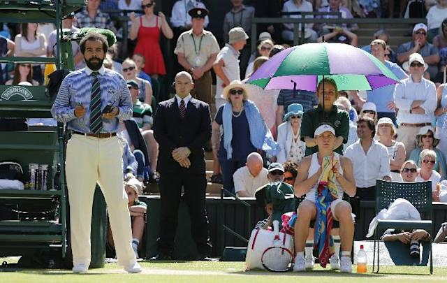 Umpire Kader Nouni, left, stands next to Simona Halep of Romania, sitting, during an interruption to take an ill woman from court during the women's singles semifinal match between Halep and Eugenie Bouchard of Canada at the All England Lawn Tennis Championships in Wimbledon, London, Thursday, July 3, 2014. (AP Photo/Ben Curtis)