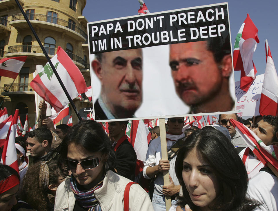 FILE - In this March 14, 2005 file photo, Lebanese opposition protesters carry a poster showing Presidents Hafez, left, and Bashar Assad during an anti-Syrian demonstration in Beirut, Lebanon. On Nov. 13, 1970, Hafez Assad a young career air force officer launched a bloodless coup. Fifty years later, Assad's family still rules Syria. The country is in ruins from a decade of civil war that killed around a half million people, displaced half the population and virtually wiped out the economy. But Hafez's son, Bashar, has an unquestioned grip on what remains. (AP Photo/Hussein Malla, File)