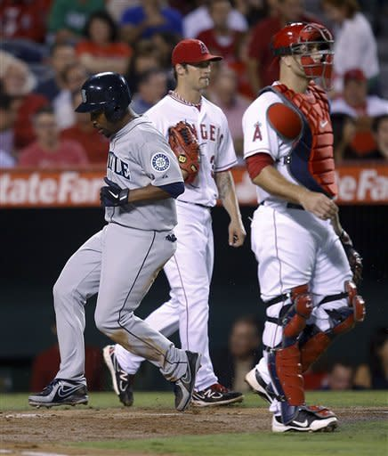 Seattle Mariners' Chone Figgins, left, scores a run past Los Angeles Angels catcher Chris Iannetta, right, and starting pitcher C.J. Wilson during the third inning of a baseball game in Anaheim, Calif., Wednesday, Sept. 26, 2012. (AP Photo/Jae C. Hong)