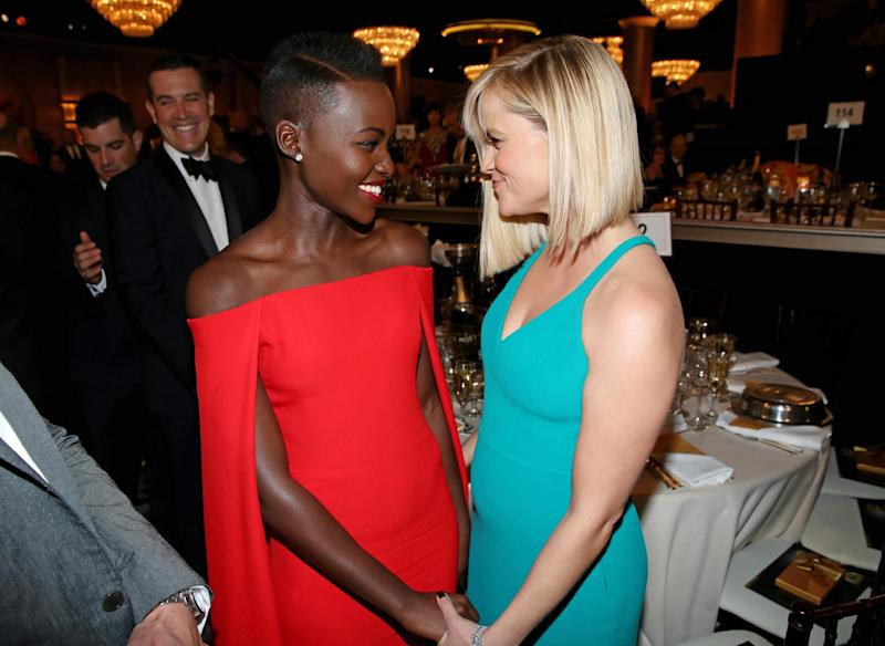 Lupita Nyong'o, left, and Reese Witherspoon speak in the audience at the 71st annual Golden Globe Awards at the Beverly Hilton Hotel on Sunday, Jan. 12, 2014, in Beverly Hills, Calif. (Photo by Matt Sayles/Invision/AP)