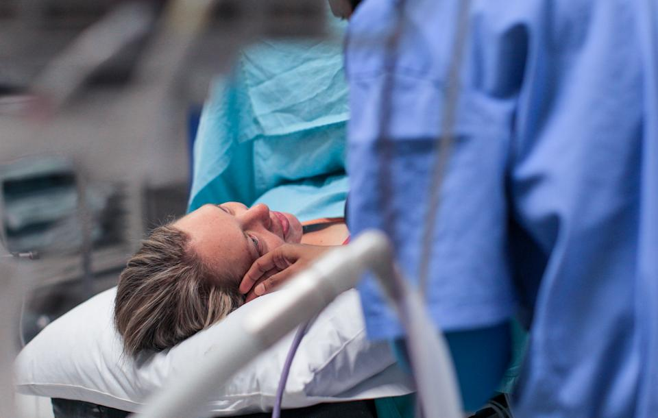 a Young pregnant woman lays on the operating table moments before a caesarean section