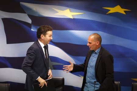 Dijsselbloem, head of the euro zone finance ministers' group, and Greek Finance Minister Yanis Varoufakis shake hands after their common press conference at the ministry in Athens