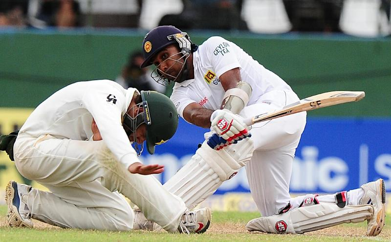 Sri Lanka batsman Mahela Jayawardene (R) plays a shot as Pakistan's Azhar Ali takes cover on the third day of the second Test at the Sinhalese Sports Club (SSC) Ground in Colombo on August 16, 2014 (AFP Photo/Lakruwan Wanniarachchi)