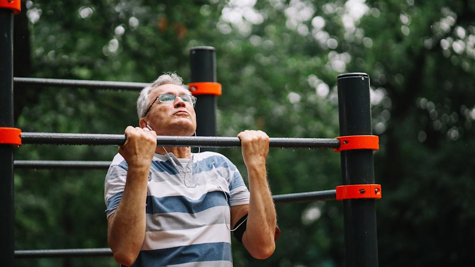 Mature man exercising in the public park, trying to stay fit and healthy at older age.