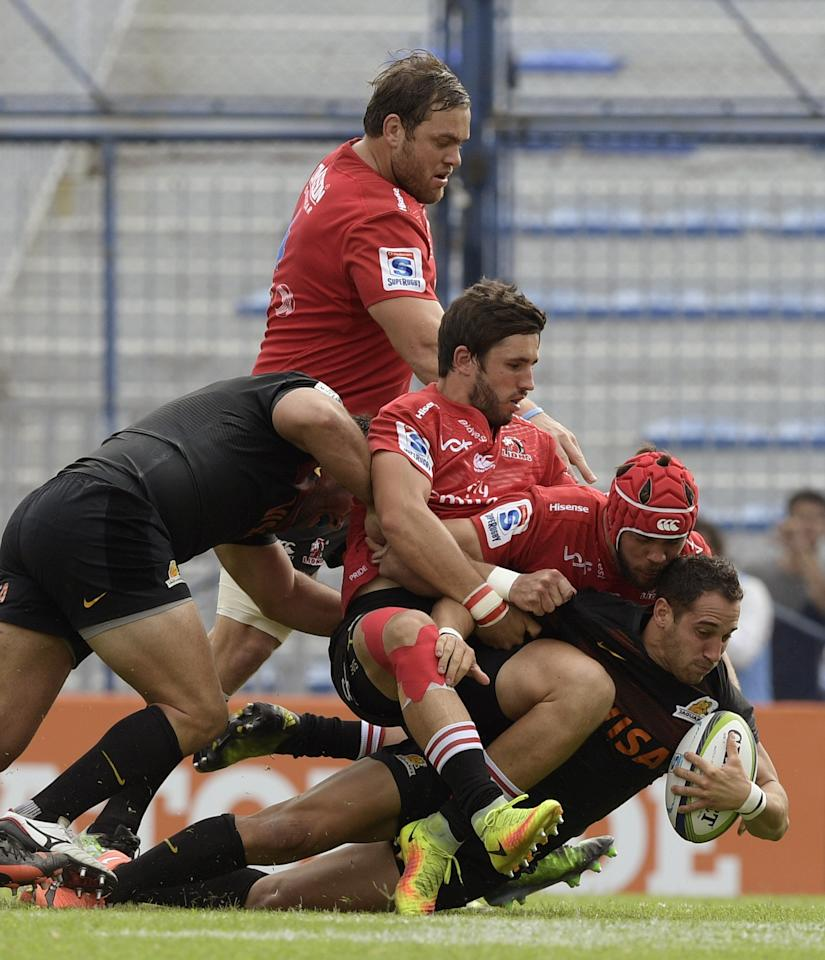 Argentina's Jaguares fullback Joaquin Tuculet (R) is tackled by South Africa's Lions N8 Warren Whiteley (2-R) and South Africa's Lions centre Jacques Nel during their Super Rugby match at Jose Amalfitani stadium in Buenos Aires on March 11, 2017. (AFP Photo/JUAN MABROMATA)