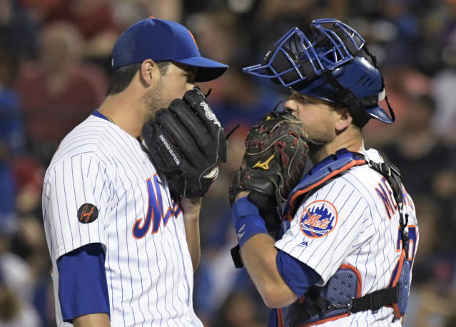 New York Mets relief pitcher Anthony Swarzak, left, talks with catcher Devin Mesoraco during the ninth inning of the team's baseball game against the Atlanta Braves on Friday, Aug. 3, 2018 in New York.the Braves won 2-1. (AP Photo/Bill Kostroun)