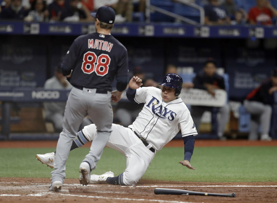 Tampa Bay Rays' Avisail Garcia scores ahead of the throw to Cleveland Indians relief pitcher Phil Maton (88) on a throwing error by first baseman Carlos Santana during the seventh inning of a baseball game Saturday, Aug. 31, 2019, in St. Petersburg, Fla. (AP Photo/Chris O'Meara)
