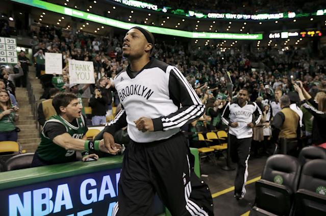 Brooklyn Nets forward Paul Pierce, front, formerly of the Boston Celtics, receives applause as he steps onto the court before an NBA basketball game against the Celtics, Sunday, Jan. 26, 2014, in Boston. (AP Photo/Steven Senne)