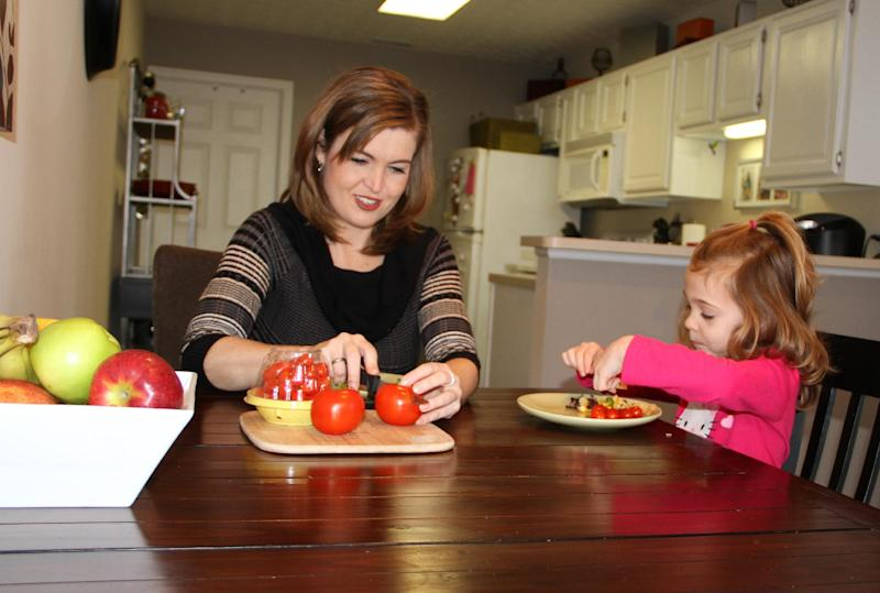 This Jan. 21, 2014 photo released by MediaSource shows Shannon McCormick, left, cutting up a tomato for her 4 year old daughter Sophie Chapman at their home in Gahanna, Ohio. Although not fond of tomatoes, McCormick keeps that fact from her daughter, who loves them. (AP Photo/MediaSource, Robert Leitch)