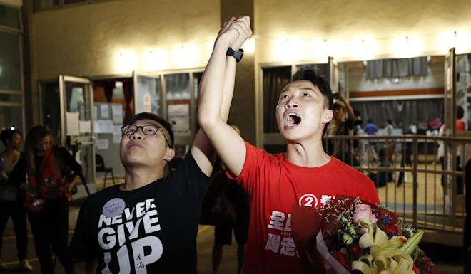 Jimmy Sham (right) celebrates with a supporter after winning a district council seat. Photo: AP