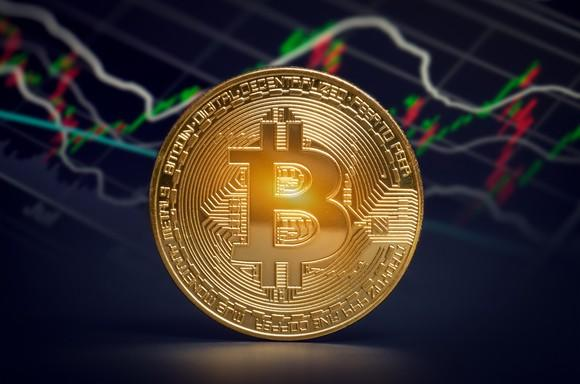 Gold coin with a bitcoin symbol on it in front of a stock chart.