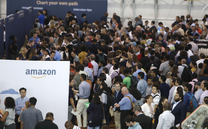 FILE - In this Sept. 17, 2019, file photo job seekers line up to speak to recruiters during an Amazon job fair in Dallas. On Friday, Oct. 4, the U.S. government issues the September jobs report. Amazon says it hired 200,000 people for the busy holiday shopping season, double the amount of people it hired last year. (AP Photo/LM Otero, File)