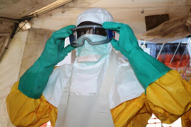 A health worker with 'Doctors Without Borders' puts on protective equipment at an Ebola isolation ward in Conakry, on June 28, 2014