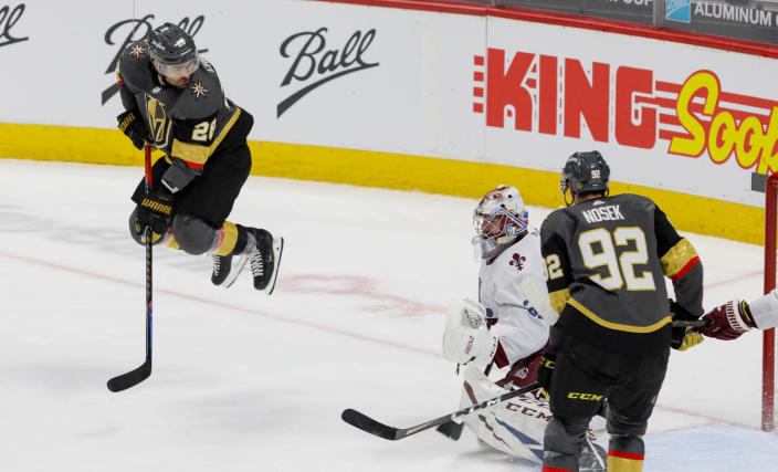Vegas Golden Knights left wing William Carrier (28) hops over a shot against Colorado Avalanche goaltender Philipp Grubauer (31) as Golden Knights left wing Tomas Nosek (92) moves in during the third period of an NHL hockey game in Denver, Saturday, March 27, 2021. (AP Photo/Joe Mahoney)