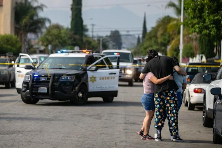 EAST LOS ANGELES, CA - JUNE 28: Neighbors embrace and the come to grips with three children being found dead at a home on South Ferris Ave in East Los Angeles on Monday, June 28, 2021 in East Los Angeles, CA. (Jason Armond / Los Angeles Times)
