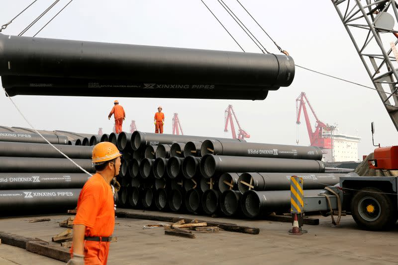 Workers direct a crane lifting ductile iron pipes for export at a port in Lianyungang, Jiangsu