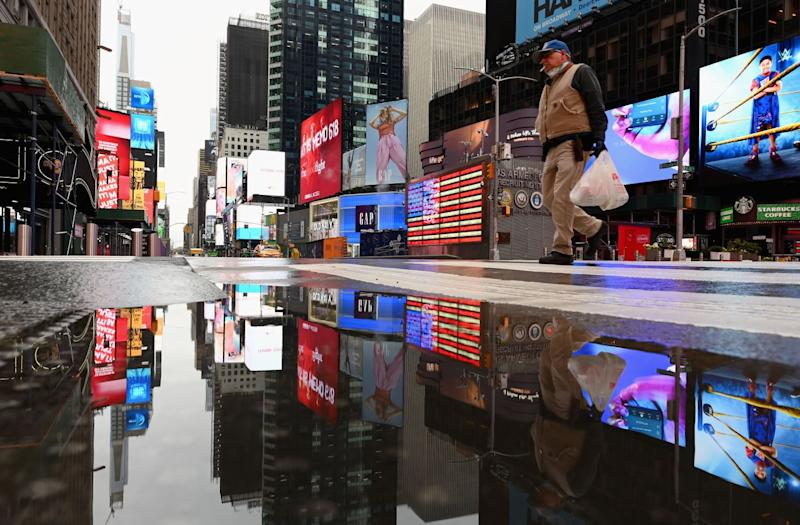 A man crosses the street at a nearly empty Times Square on Thursday in New York City.