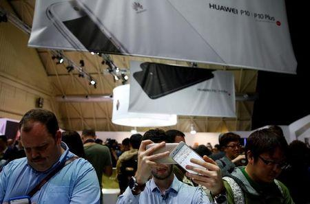 A man takes pictures of Huawei's new P10 Plus device after its presentation ceremony at Mobile World Congress in Barcelona, Spain, February 26, 2017. REUTERS/Paul Hanna/Files