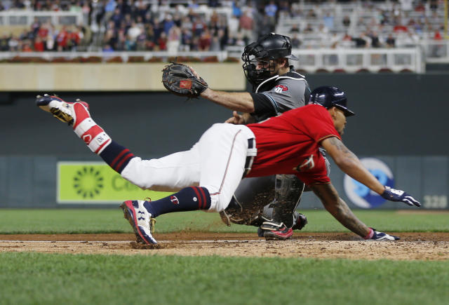 Byron Buxton beats the tag by Diamondbacks catcher Chris Iannetta to complete an inside-the-park home run. (AP)