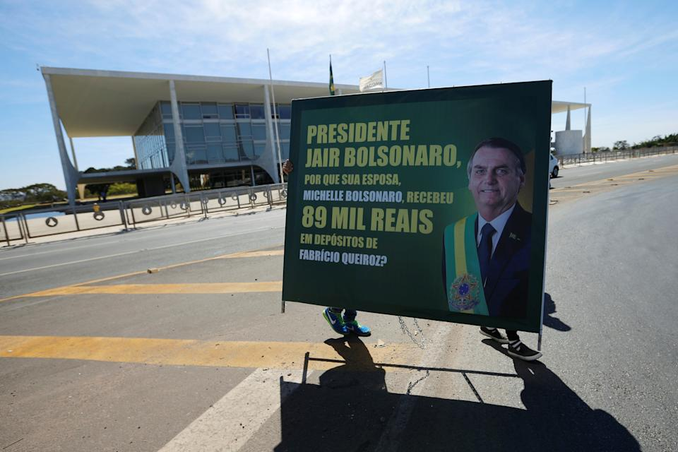 """Demonstrators hold a banner reading """" President Jair Bolsonaro, why  your wife Michelle Bolsonaro received 89 thousand reais in deposit from Fabricio Queiroz? """" during a protest against Brazil's President Jair Bolsonaro in front of Planalto Palace in Brasilia, Brazil August 27, 2020. REUTERS/Adriano Machado"""