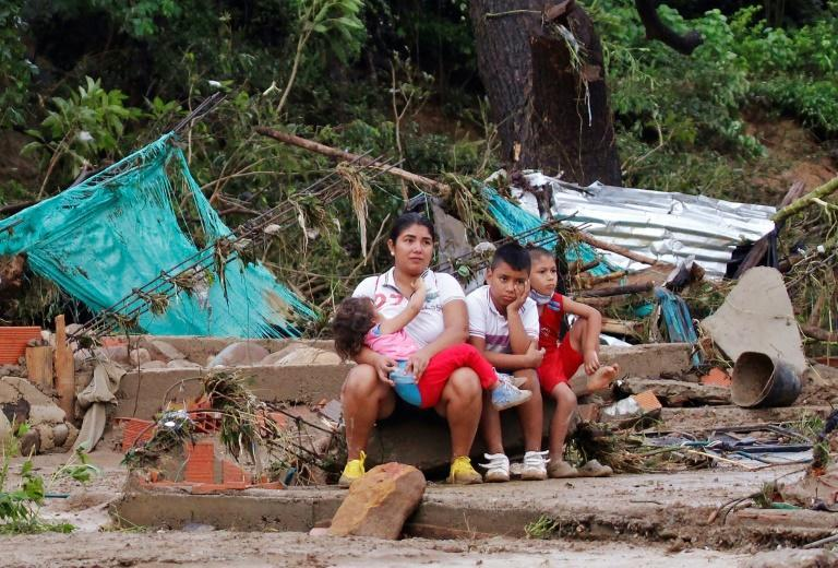 A woman and her chidren sit on the remains of a house destroyed by heavy rains and flooding in Cucuta, Colombia, on November 18, 2020