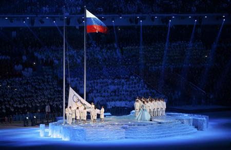 The Olympic flag is raised next to the flag of Russia during the opening ceremony of the 2014 Sochi Winter Olympics, February 7, 2014. REUTERS/Mark Blinch (