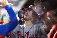 Philadelphia Phillies' J.T. Realmuto celebrates with teammates in their dugout after scoring a home run during the seventh inning of a baseball game against the Washington Nationals in Washington, Tuesday, Aug. 3, 2021. (AP Photo/Manuel Balce Ceneta)