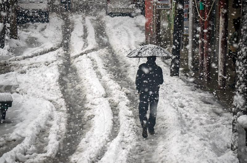2019/11/09: A resident walks along a snow covered road while holding an umbrella during the heavy snowfall in Kashmir. (Photo: SOPA Images via Getty Images)