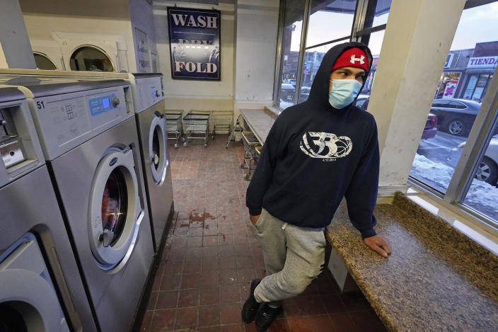 """Cesar Osorio, a 30-year-old construction worker, waits for his clothes to dry at a laundromat in Chelsea, Mass., Feb. 10, 2021. Osorio said he and his family contracted the coronavirus last spring and recovered fairly quickly using home remedies like tea with honey. """"If the government told me I must take the vaccine, then I'd take it, sure. But at the moment, I don't want it,"""" he said. """"Spanish people, we have our own medicines. We don't want vaccines."""" (AP Photo/Elise Amendola)"""