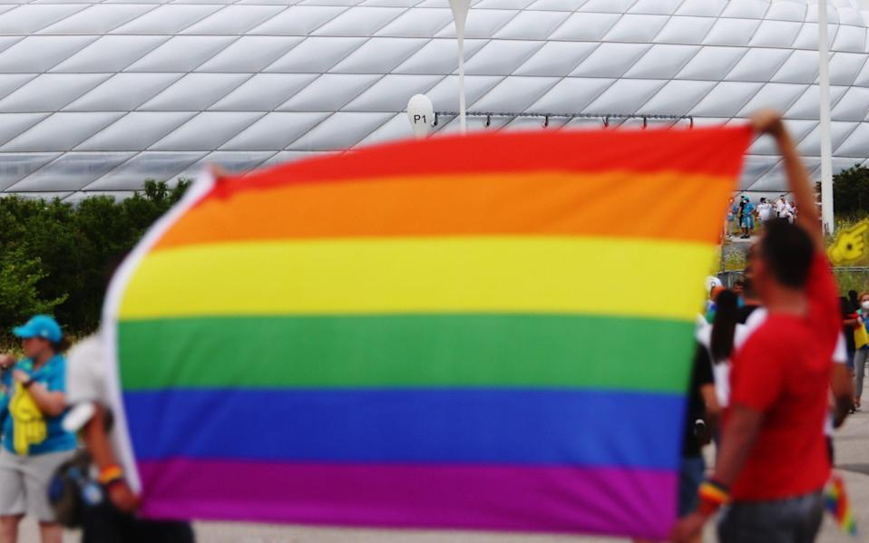 Fans hold rainbow flags outside the stadium before the matc - Reuters