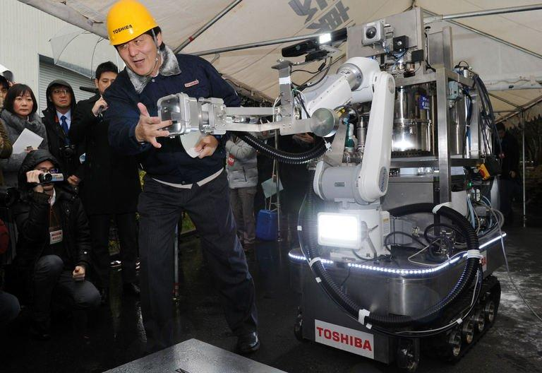 An engineer of Toshiba displays a decontamination robot, for work inside a nuclear plant, during a demonstration at Toshiba's technical center in Yokohama, suburban Tokyo on February 15, 2013. The crawler robot blasts dry ice particles against contaminated floors or walls and will be used for the decontamination in TEPCO's stricken Fukushima nuclear power plant