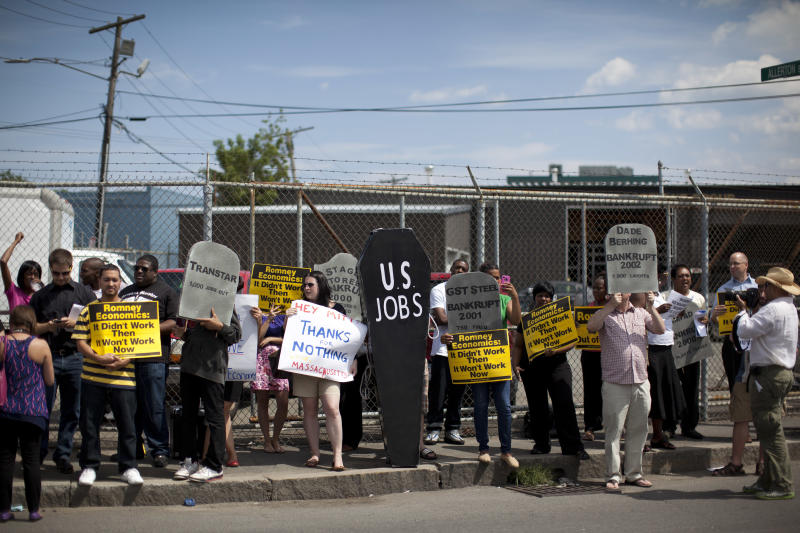 Protestors stands outside Middlesex Truck and Coach during a visit by Republican presidential candidate, former Massachusetts Gov. Mitt Romney, Thursday, July 19, 2012, in Roxbury, Mass. (AP Photo/Evan Vucci)