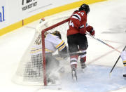 New Jersey Devils left wing Miles Wood (44) sends Boston Bruins goaltender Tuukka Rask (40) into the net during the first period of an NHL hockey game Thursday, Jan. 14, 2021, in Newark, N.J. Wood received a two-minute penalty for interference. (AP Photo/Bill Kostroun)