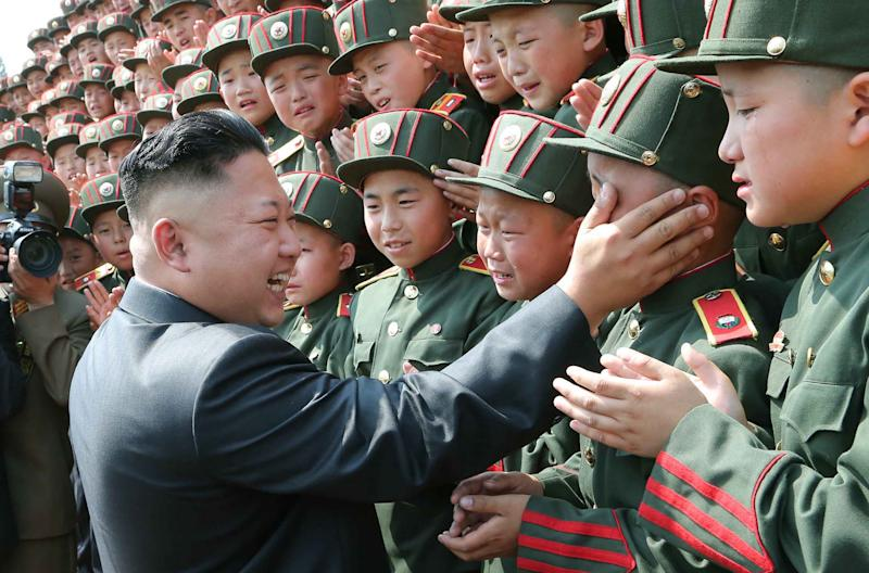 This undated picture released from North Korea's official Korean Central News Agency (KCNA) on June 7, 2014 shows Kim Jong-Un greeting soldiers during a visit to the Mangyongdae Revolutionary School in Pyongyang (AFP Photo/)
