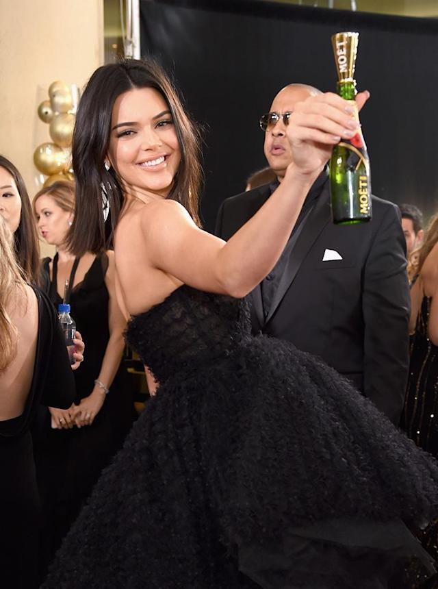 "<p>The model made her Golden Globe debut at Sunday's event, with champagne in hand. Don't worry: She <a href=""https://sg.news.yahoo.com/kendall-jenners-ginormous-golden-globes-dress-required-someone-hold-train-053918510.html"" data-ylk=""slk:had someone to help her;outcm:mb_qualified_link;_E:mb_qualified_link"" class=""link rapid-noclick-resp newsroom-embed-article"">had someone to help her</a> manuever around the Beverly Hills Hilton ballroom in that massive gown. (Photo: Michael Kovac/Getty Images for Moet & Chandon) </p>"