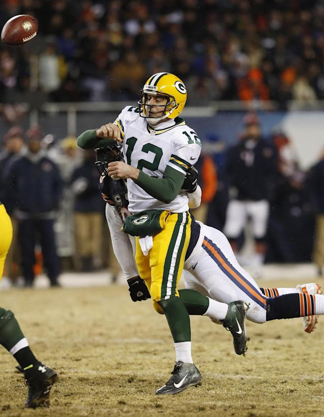 Green Bay Packers quarterback Aaron Rodgers (12) gets hit from behind by Chicago Bears defensive end Julius Peppers as he gets off a pass during the first half of an NFL football game, Sunday, Dec. 29, 2013, in Chicago. (AP Photo/Charles Rex Arbogast)