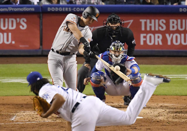 San Francisco Giants' Joe Panik, second from left, hits a solo home run as Los Angeles Dodgers relief pitcher Kenley Jansen, left, pitches and catcher Yasmani Grandal, right, watches along with home plate umpire Jim Reynolds during the ninth inning of a baseball game Saturday, Dec. 31, 2016, in Los Angeles. (AP Photo/Mark J. Terrill)