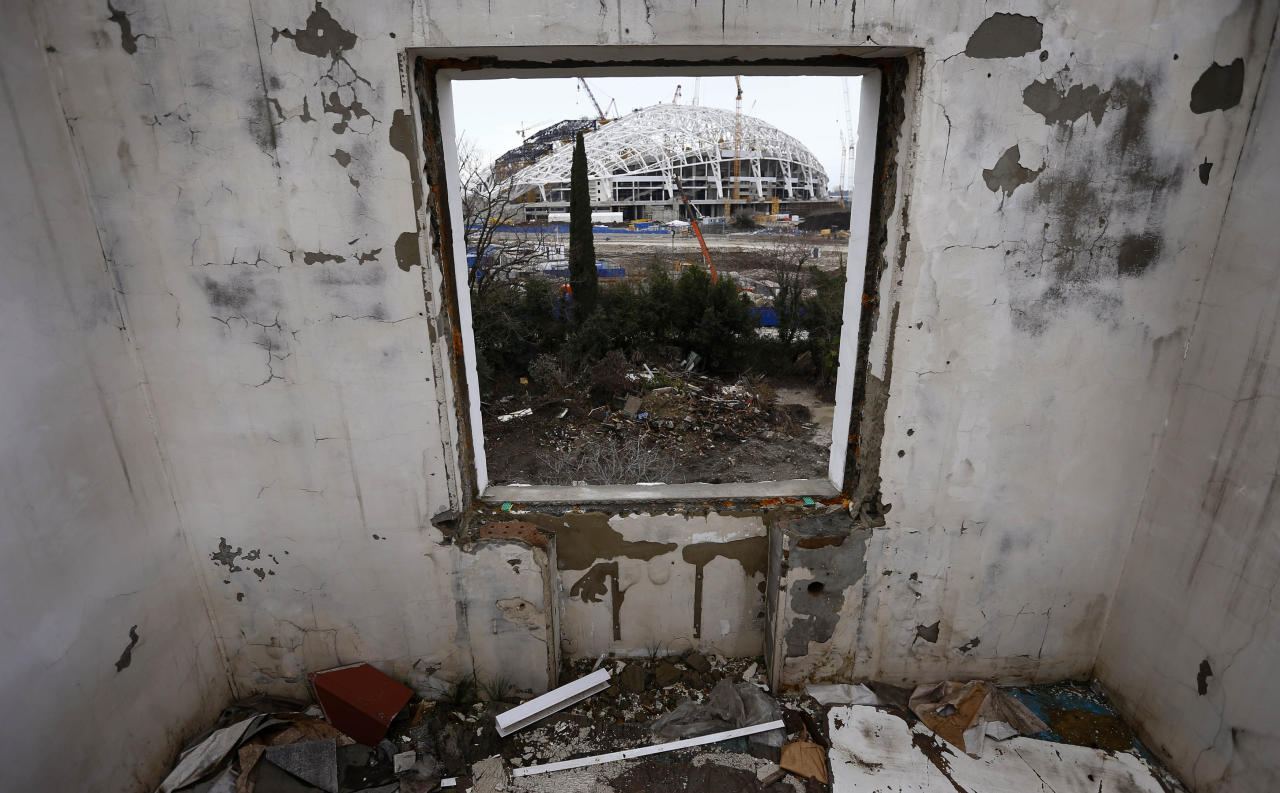 A picture shot through the window of a house that has to be torn down as it is within the perimeters of the Olympic Park shows the Olympic stadium for the Sochi 2014 Winter Olympics at the Olympic Park in Adler, near Sochi February 18, 2013. Although many complexes and venues in the Black Sea resort of Sochi mostly resemble building sites that are still under construction, there is nothing to suggest any concern over readiness. Construction will be completed by August 2013 according to organizers. The Sochi 2014 Winter Olympics opens on February 7, 2014. REUTERS/Kai Pfaffenbach (RUSSIA - Tags: BUSINESS CONSTRUCTION ENVIRONMENT SPORT OLYMPICS) - RTR3DYR7