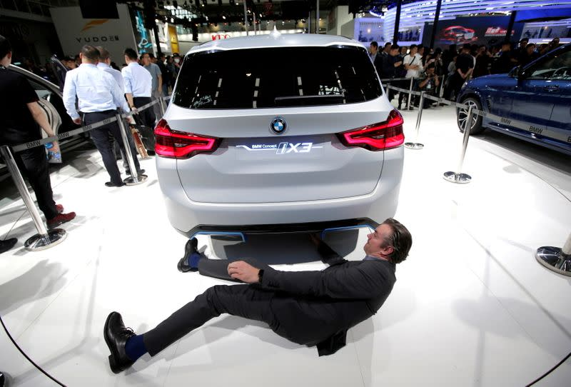 FILE PHOTO: A man checks the BMW iX3 electric concept car during a media preview at the Auto China 2018 motor show in Beijing