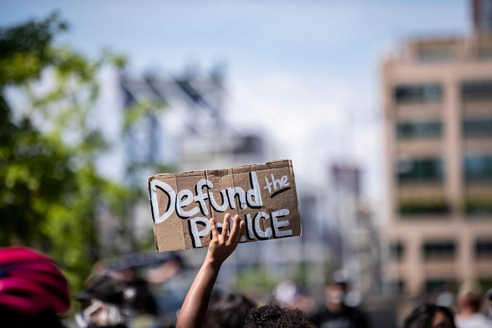 """A protester holds up a homemade sign that says, """"Defund the Police"""" during a peaceful protest in New York City June 19, 2020."""