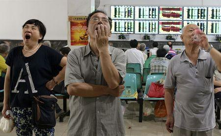 Investors look at computer screens showing stock information at a brokerage house in Wuhan, Hubei province, China, July 3, 2015. REUTERS/China Daily