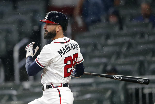 FILE - In this April 4, 2019, file photo, Atlanta Braves' Nick Markakis follows through on a three-run double in the fifth inning of baseball game against the Chicago Cubs in Atlanta. The Braves have re-signed outfielder Markakis and catcher Tyler Flowers to $4 million, one-year contracts for 2020 after declining their $6 million team options, which triggered $2 million buyout. (AP Photo/John Bazemore, File)