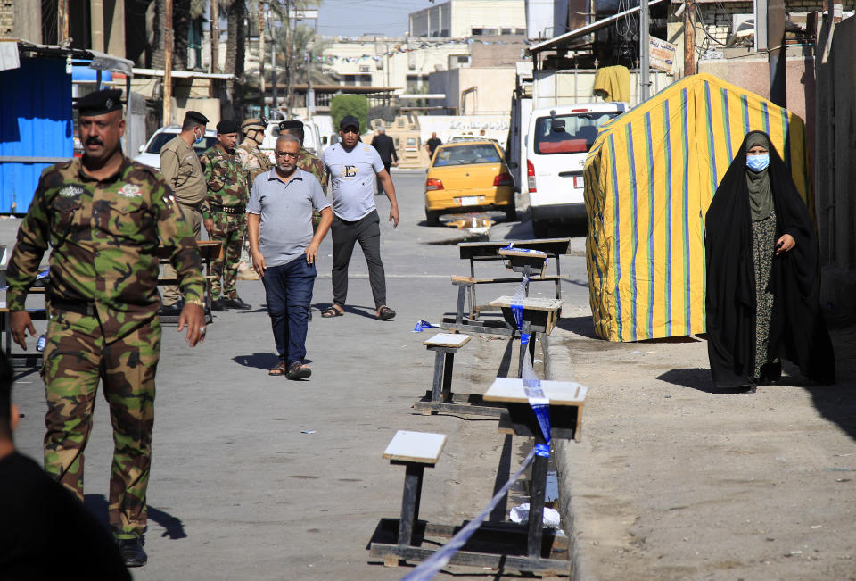 Security forces stand guard outside a polling center duringin the country's parliamentary elections in Baghdad, Iraq, Sunday, Oct. 10, 2021. Iraq closed its airspace and land border crossings on Sunday as voters headed to the polls to elect a parliament that many hope will deliver much needed reforms after decades of conflict and mismanagement. (AP Photo/Hadi Mizban)