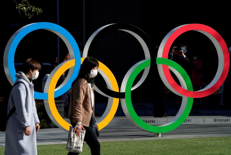 FILE PHOTO: Women wearing protective face masks following an outbreak of the coronavirus disease walk past the Olympic rings in Tokyo