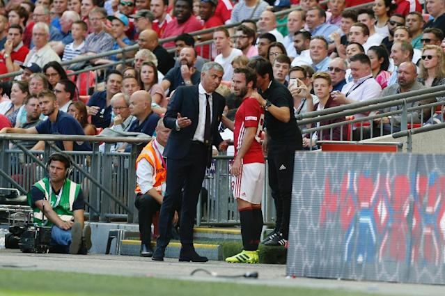 Manchester United's manager Jose Mourinho (L) talks with midfielder Juan Mata (R) after Mata was substituted on August 7, 2016 (AFP Photo/Ian Kington)