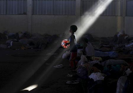 A Rohingya boy, who recently arrived in Indonesia by boat, holds his ball as he walks at a shelter in Kuala Langsa, in Indonesia's Aceh Province, May 19, 2015. REUTERS/Beawiharta
