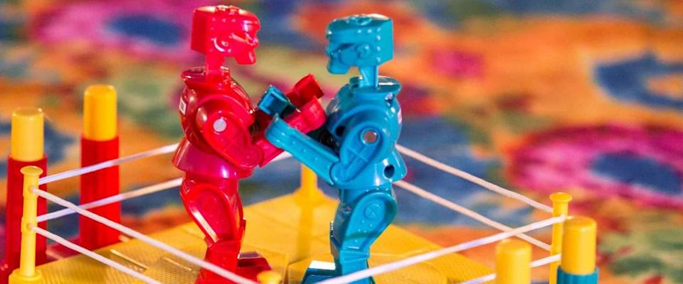 Kids brightly colored boxing robots game on multicolored table top.