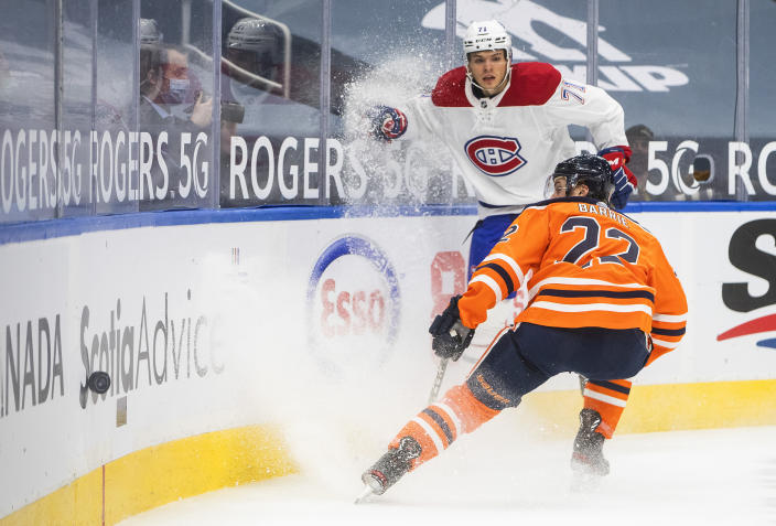 Edmonton Oilers' Tyson Barrie (22) and Montreal Canadiens' Jake Evans (71) battle for the puck during first-period NHL hockey game action in Edmonton, Alberta, Saturday, Jan. 16, 2021. (Jason Franson/The Canadian Press via AP)