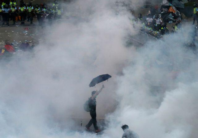 A protester walks in tear gas fired by riot policemen after thousands of protesters blocking the main street to the financial Central district outside the government headquarters in Hong Kong September 28, 2014.